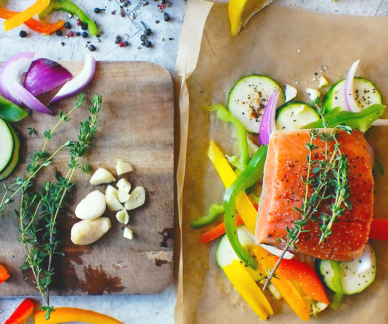 bright orange salmon arranged on a sheet of parchment paper, surrounded by sliced zucchini, bell peppers and onions next to a cutting board with more freshly sliced veggies, garlic and herbs