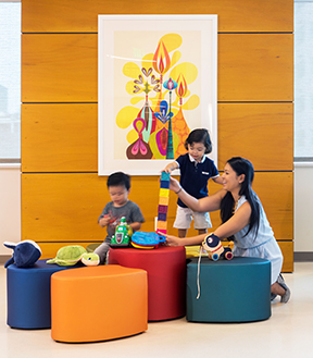 A mother and two children playing with colorful blocks