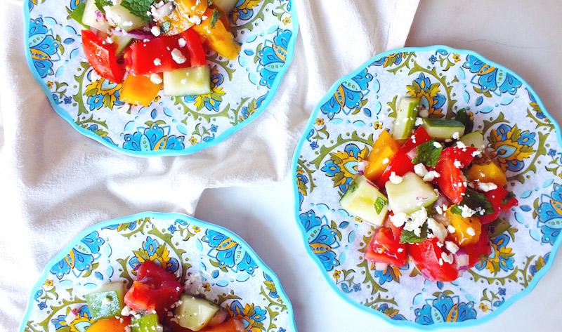 Three colorful plates of Tomato, Cucumber & Feta Summer Salad on a marble counter top and white dish towel
