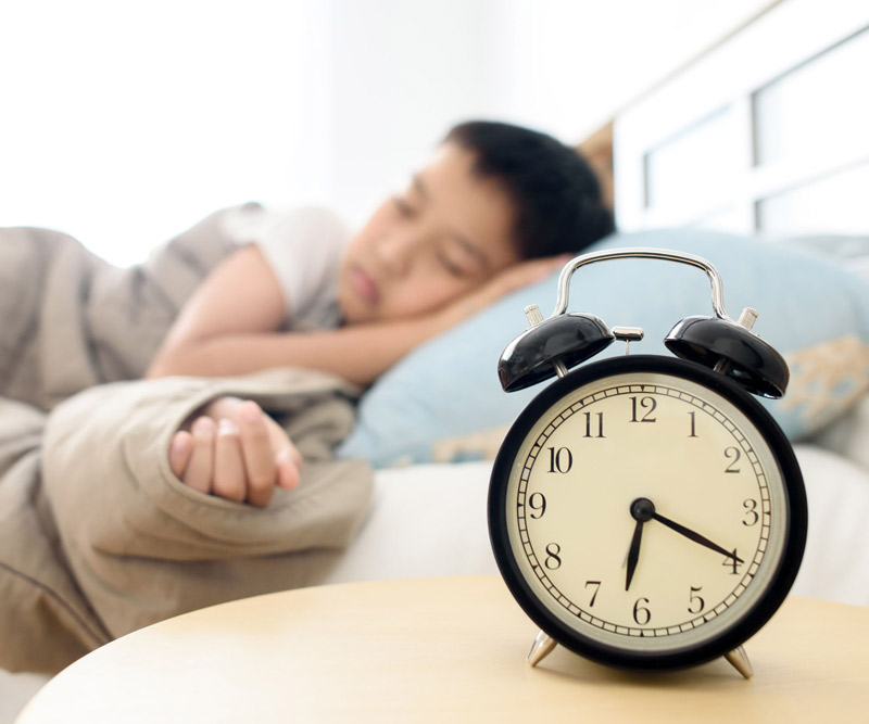 child sleeping near alarm clock