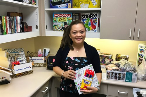 Maria Chorney displays some of the activities, including coloring books and board games, as part of the Antepartum Program at Kapiolani.