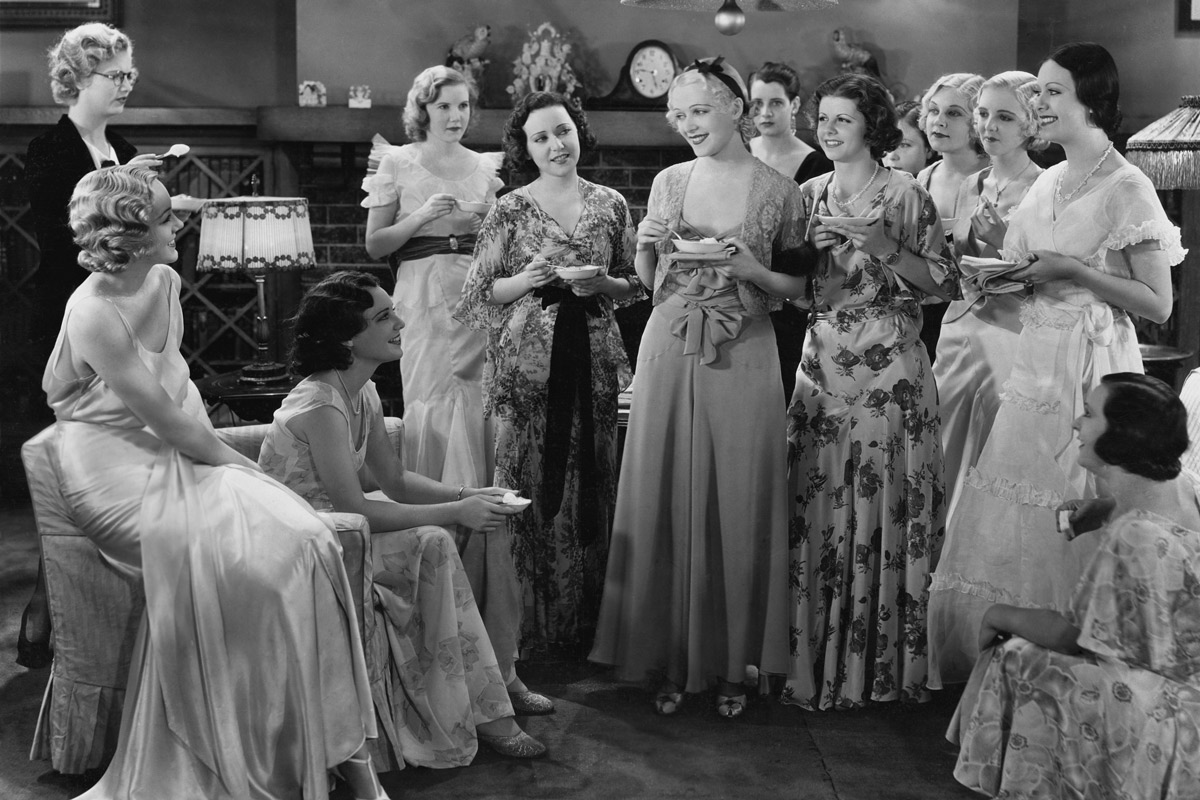 black and white photograph of a group of women at a dinner party