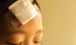 close-up of a child with a large bandage on his head