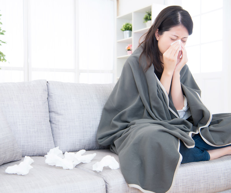 woman with a cold sits on her couch