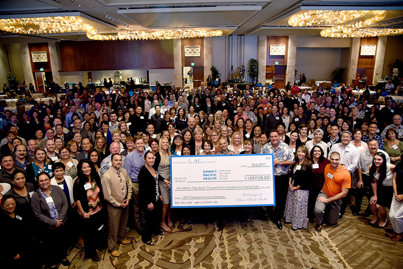 a very large group of people holding up a donation check