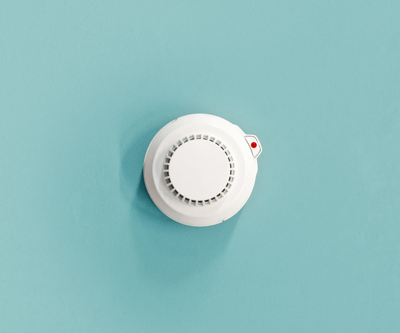 an overhead view of a smoke detector mounted on a teal ceiling