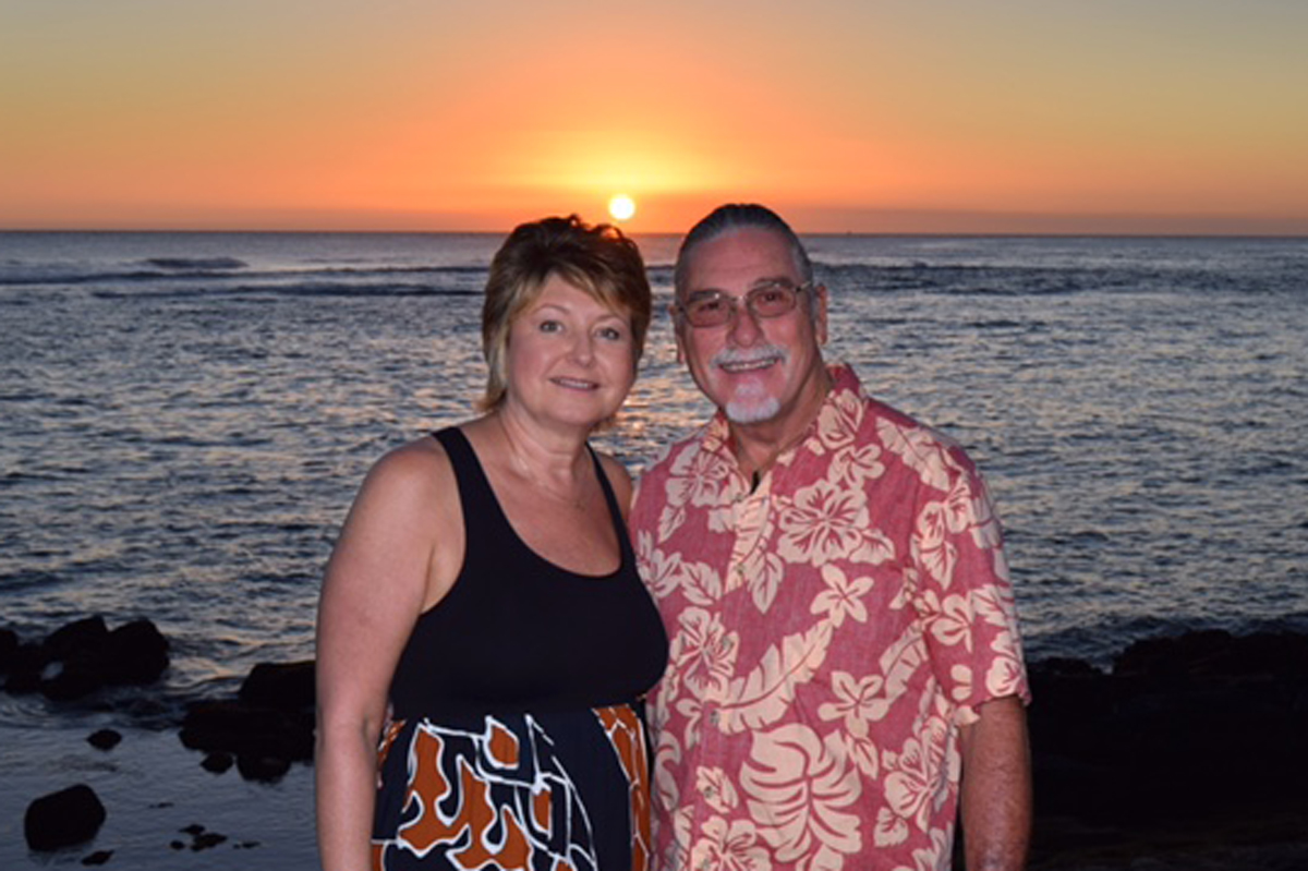 Lorri Pilkington and her husband, Larry, standing by a beach during sunset