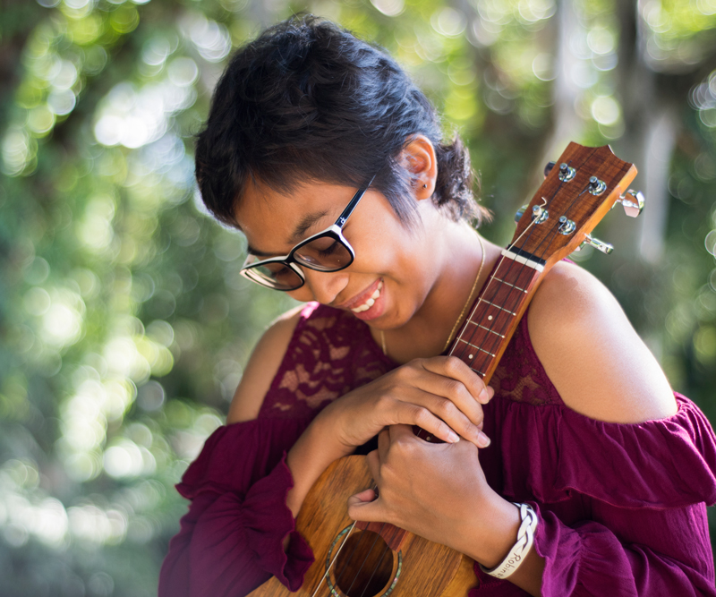 A young girl with short brown hair and glasses smiles while holding an ukulele.