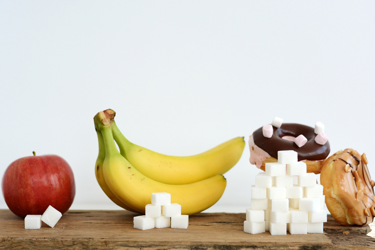 A photo shows an apple, banana and donuts with sugar cubes to depict how much sugar is found in each food item.