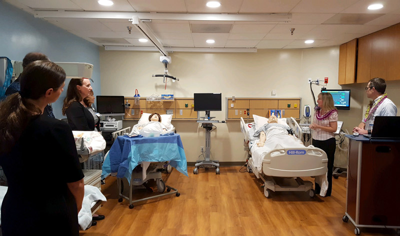 A group of people stands in a room watching a demonstration of new medical equipment and simulation manikins