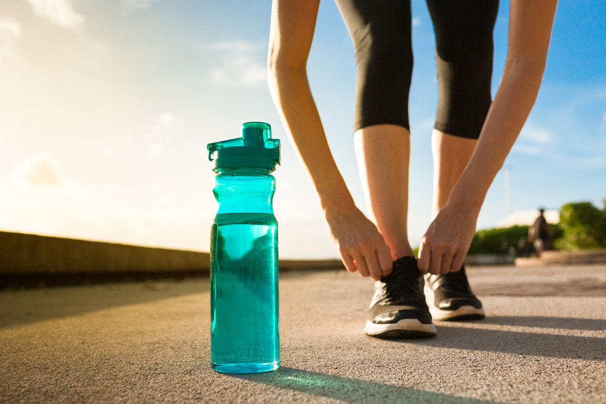 A runner laces up her shoes while a bright turquoise water bottle sits on the ground next to her.