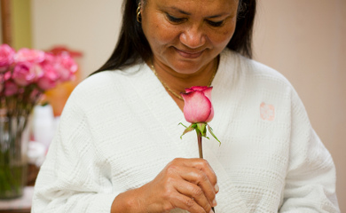 women smelling a pink rose