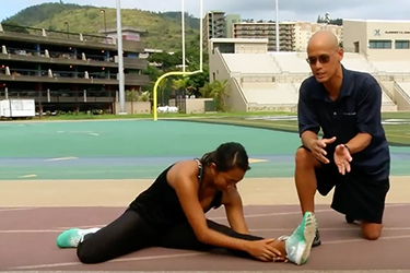 two people stretching on a track