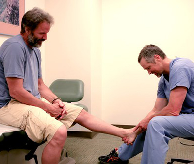 Man getting his ankle examined by doctor