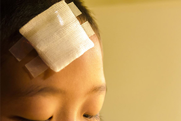 Boy with a bandage on his forehead