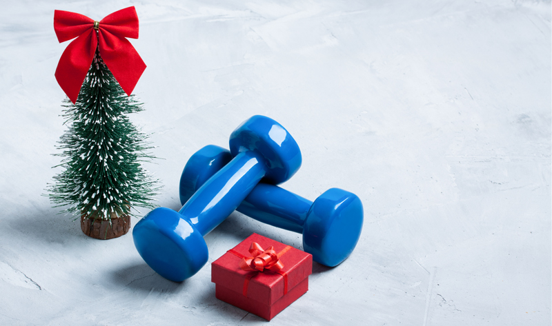dumbbells next to a mini Christmas tree and wrapped gift