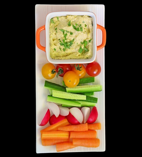 Another smart snack option – homemade hummus with colorful, fresh veggies.