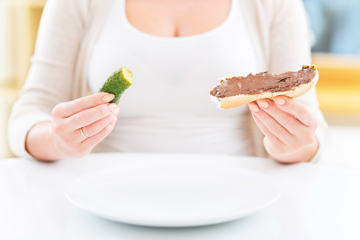 Woman holding a pickle and chocolate chocolate sandwich