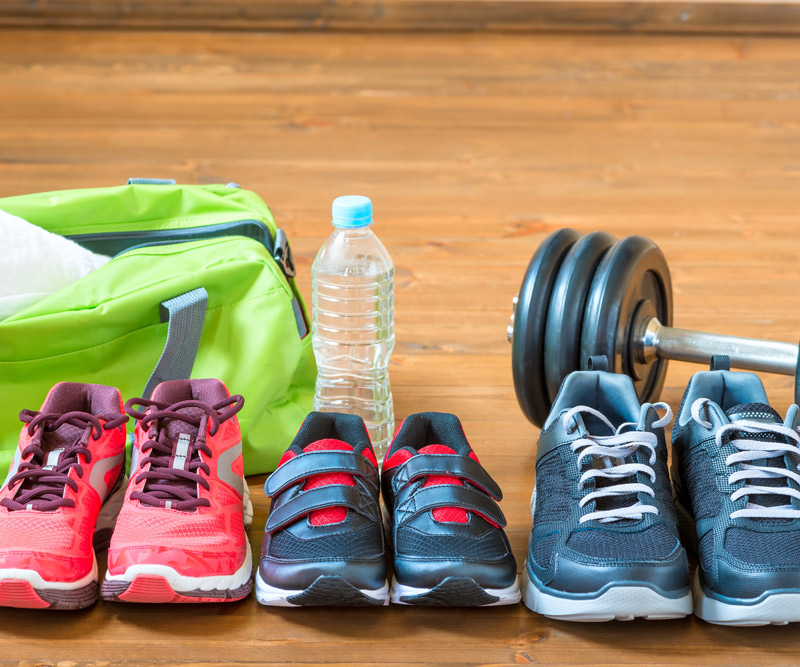 A pair of woman's, child's and man's running shoes sit in front of a gym bag, water bottle and weights to represent a family getting into shape together.