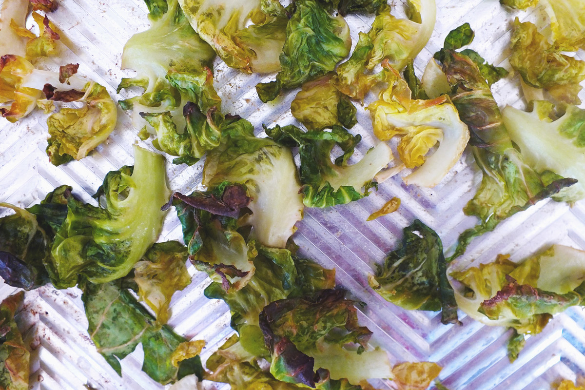 Crispy Brussels Sprout Chips on a baking sheet