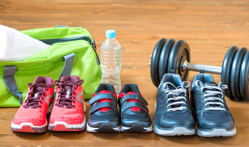 A pair of woman's, child's and man's running shoes sit in front of a gym bag, water bottle and weights to represent a family getting into shape together