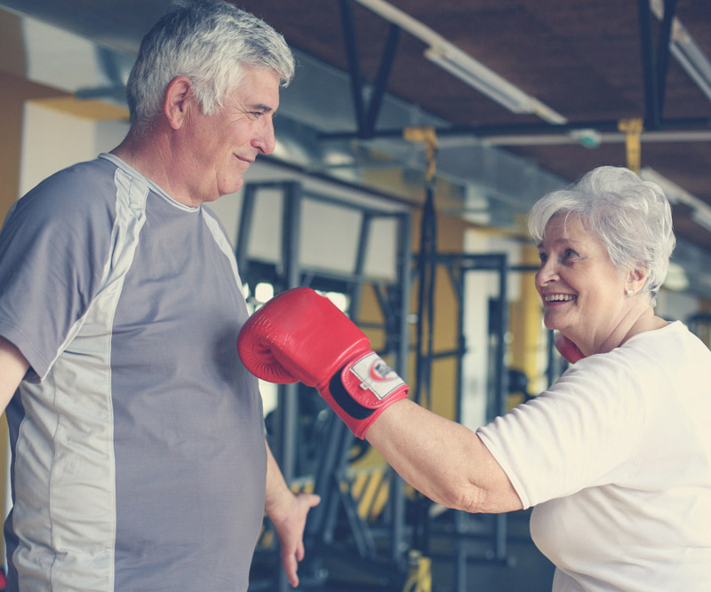 An older women playfully spars with her husband in a gym