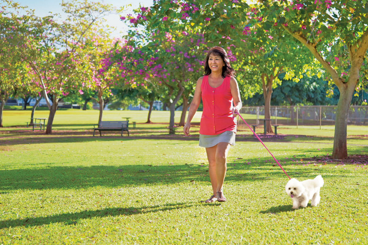 Coleen Uyechi walking her dog in a park