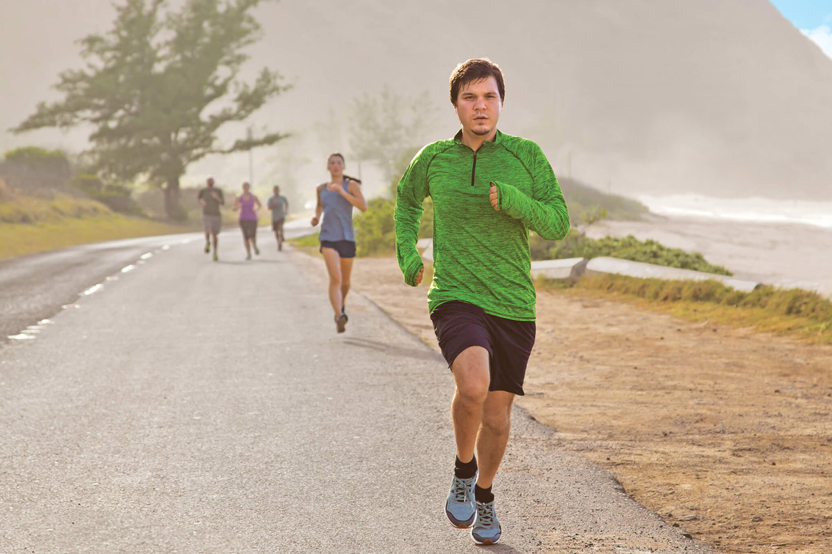 Casey Emmons running with a group of people by a beach
