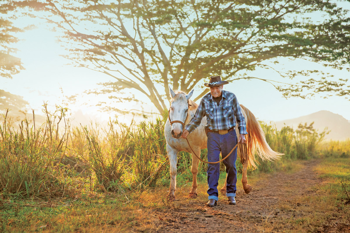 William Martin walking his horse on a trail on Kauai