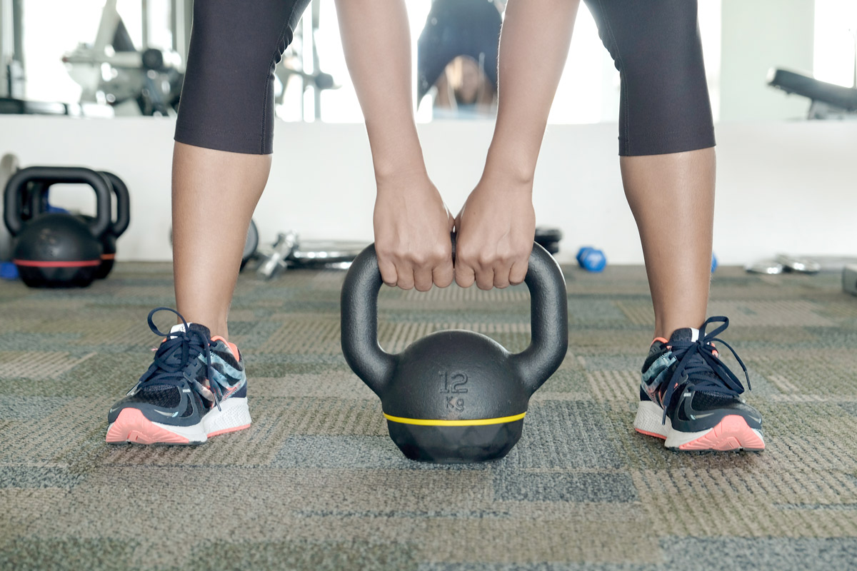 Athletic woman bending over to pick up a kettlebell