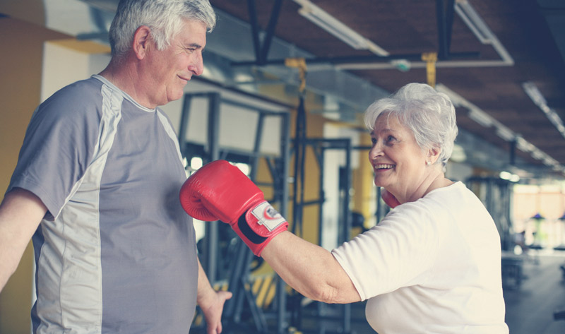 An elderly couple playfully boxing together in a gym