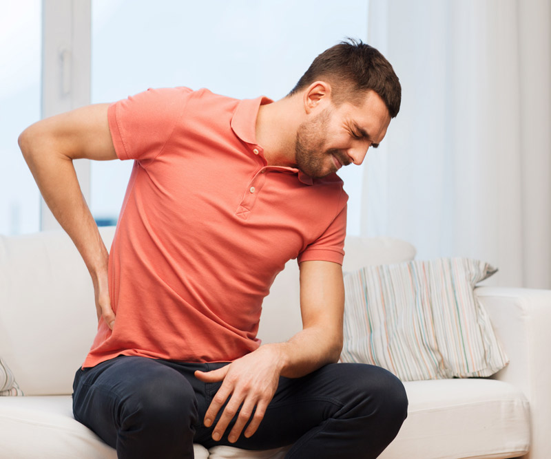 A young man sitting on a couch holding his lower back in pain