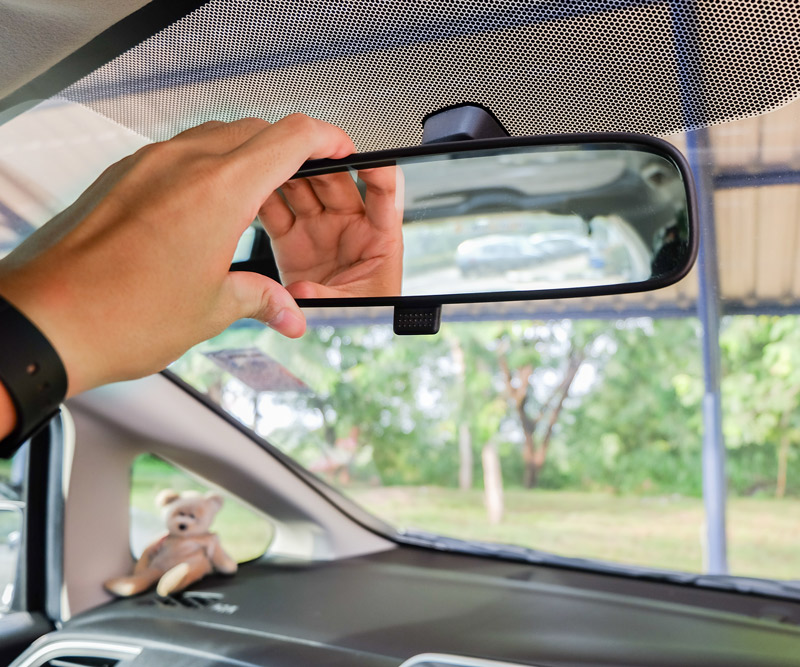 A man adjusts his review mirror of his car to better see out the back window
