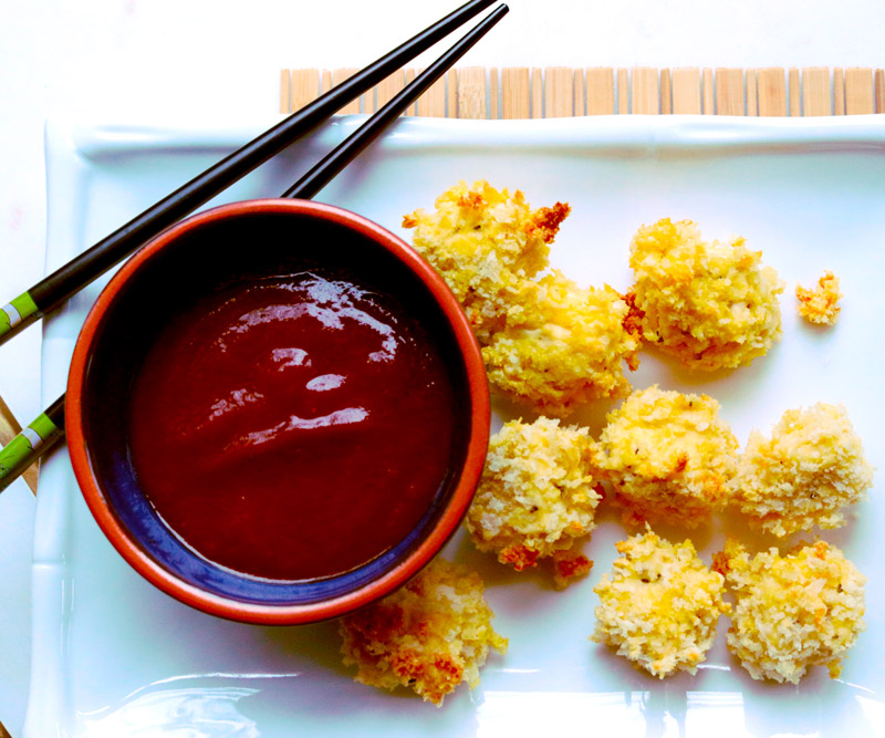A pair of chopsticks rests on a serving dish with pieces of Tofu Katsu and a bowl of homemade Katsu Sauce