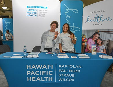 Two women standing behind the Women's Center Booth at the Great Aloha Run Expo