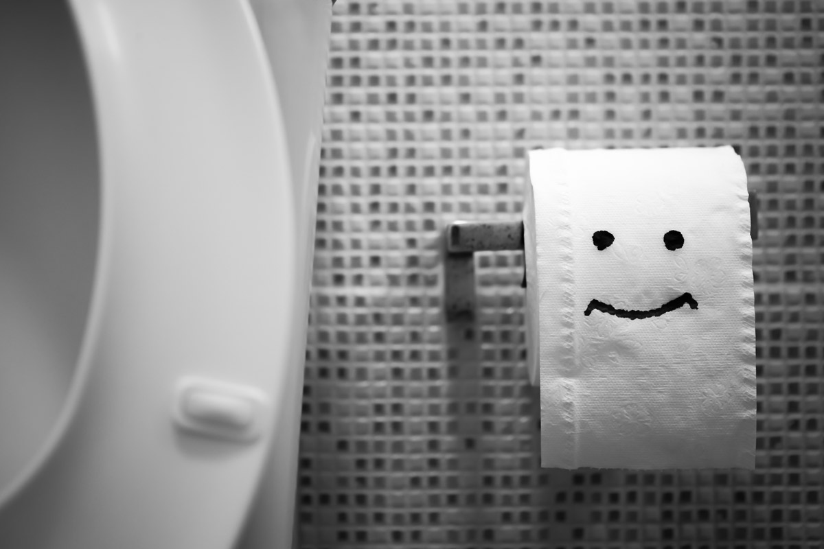 Close-up of a happy face drawn on a roll of toilet paper