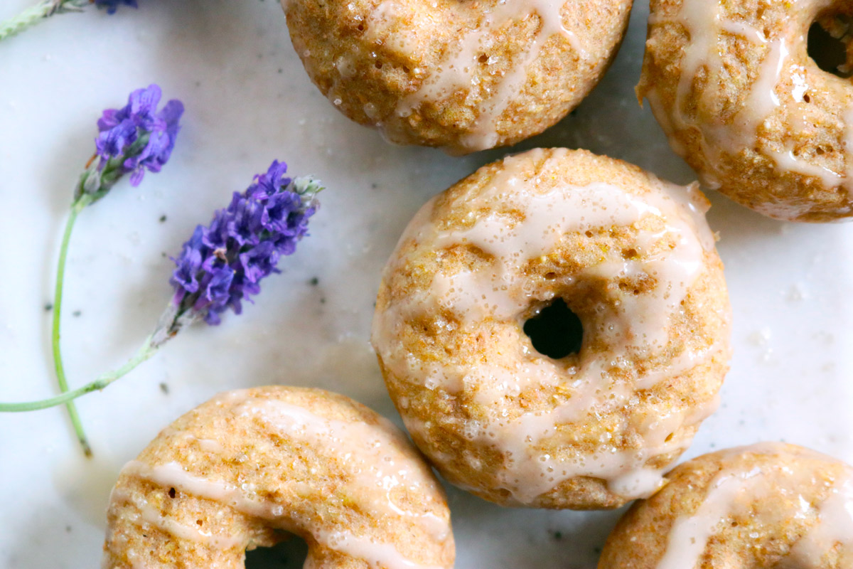 A batch of Baked Lavender & Rose Donuts are displayed on a counter top with fresh sprigs of lavender next to them