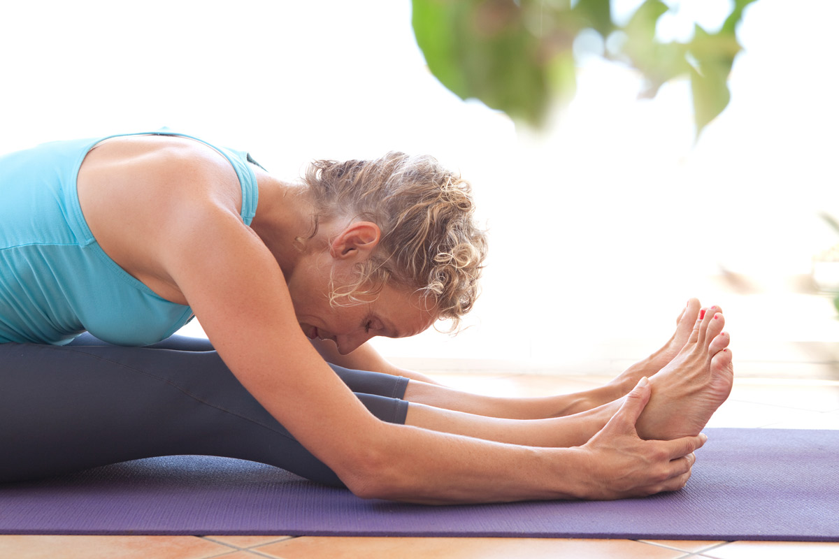 an older woman bends forward into a yoga position