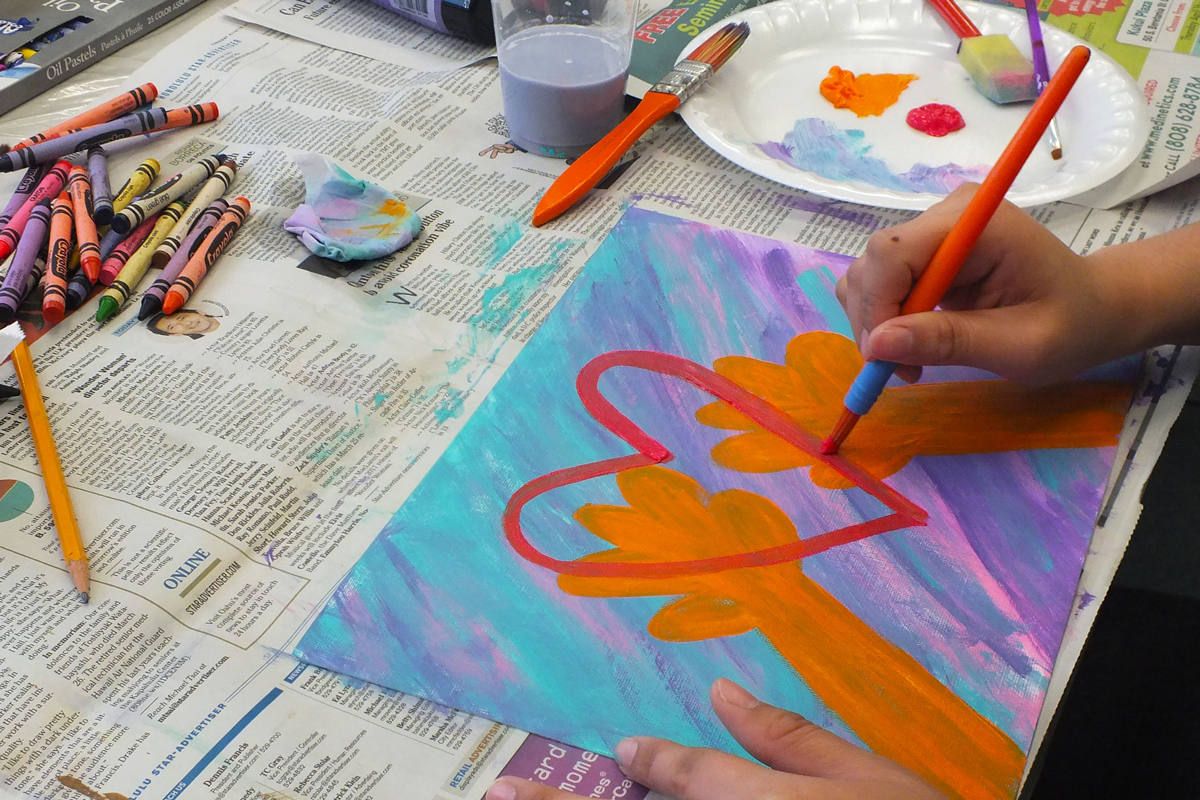 A cancer patient paints a heart on a colorful canvas.