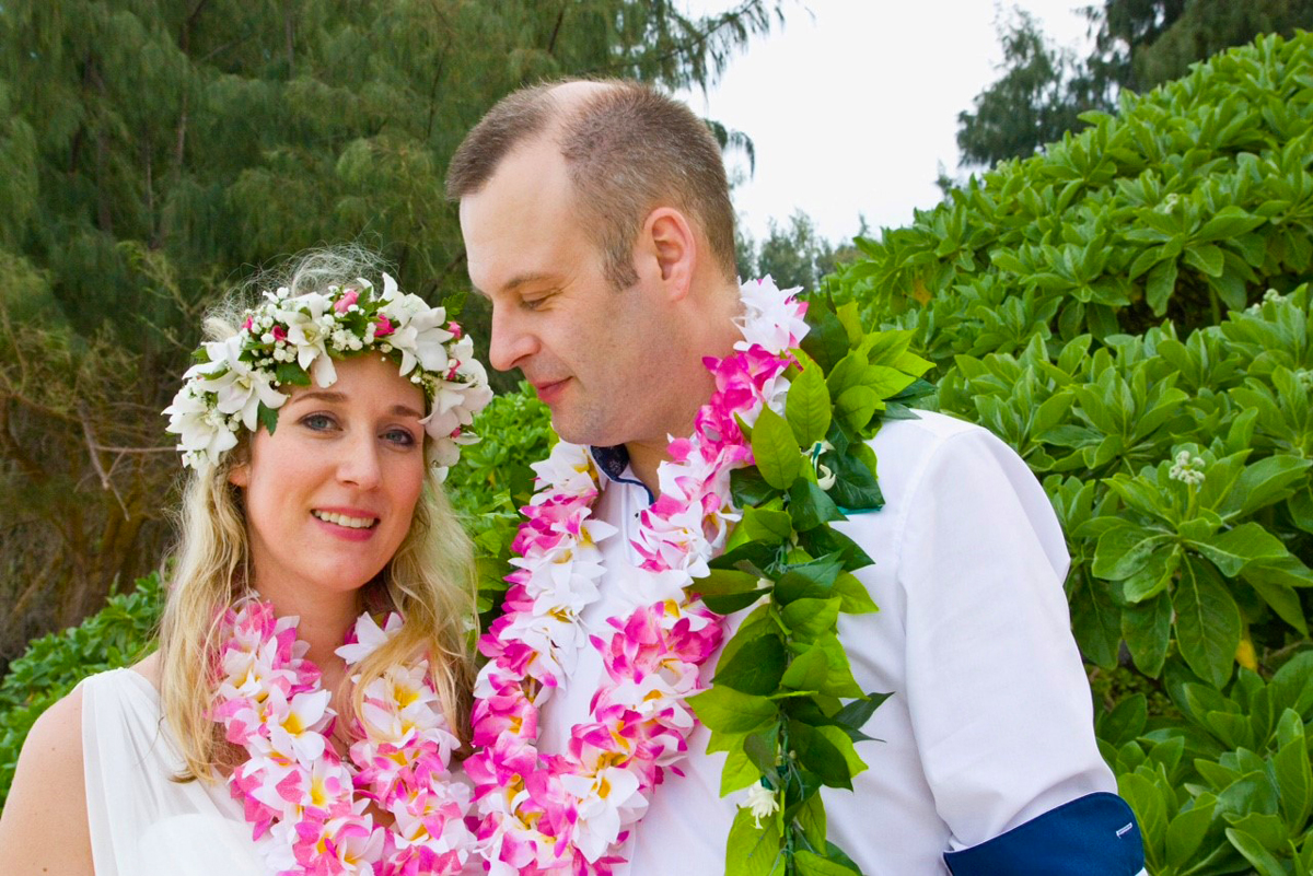 Wearing pink flower lei and dressed in white, Sinah Meier and Olli Fuchs pose for their wedding photos on the beach in Hawaii