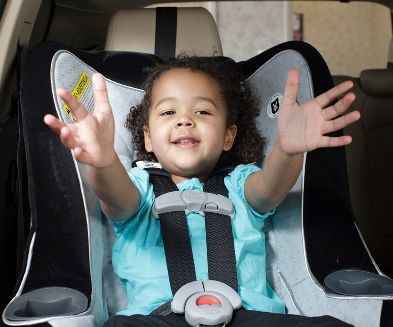 Child sitting in a forward-facing car safety seat