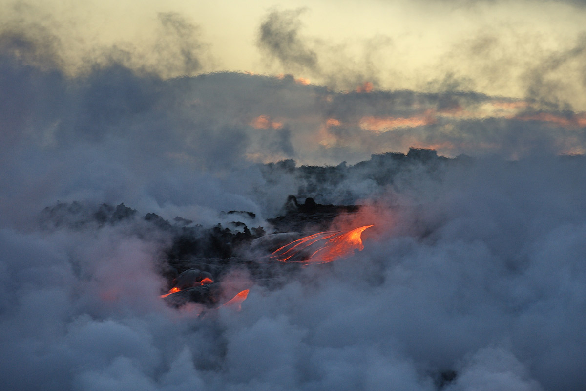 a thick layer of vog clouds the air around an active lava field