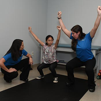 Physiotherapist and doctor exercising with young patient