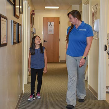 Physical therapist and young patient walking in the hallway of the Bone and Joint Center
