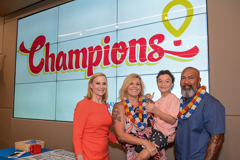 Two women, child and man in front of screen with Children's Miracle Network Hospitals Champions logo