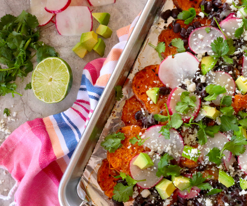 a sheet pan of Loaded Sheet Pan Sweet Potato Nachos sits on a brightly colored hand towel on a kitchen counter