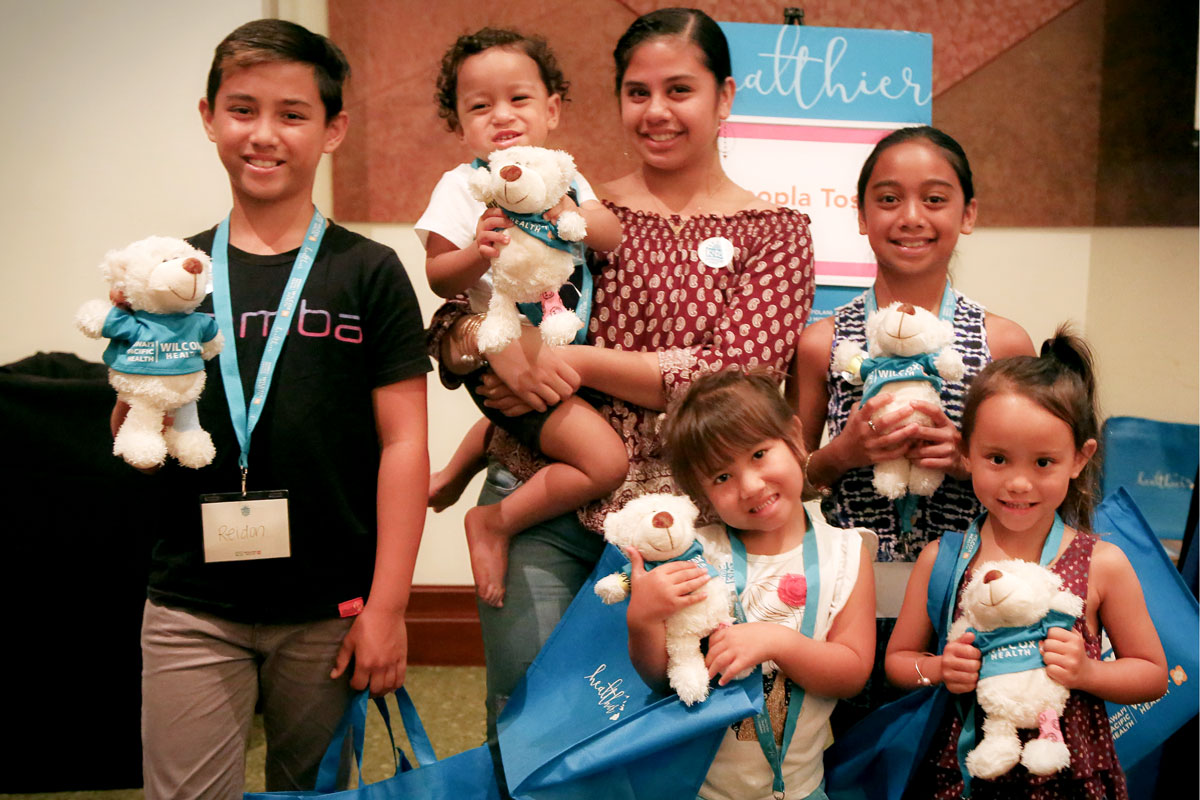 a mother and her five children smile while holding teddy bears and Kids Summer Fest tote bags