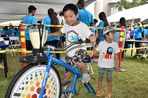Boy riding the blender bike at kids fest