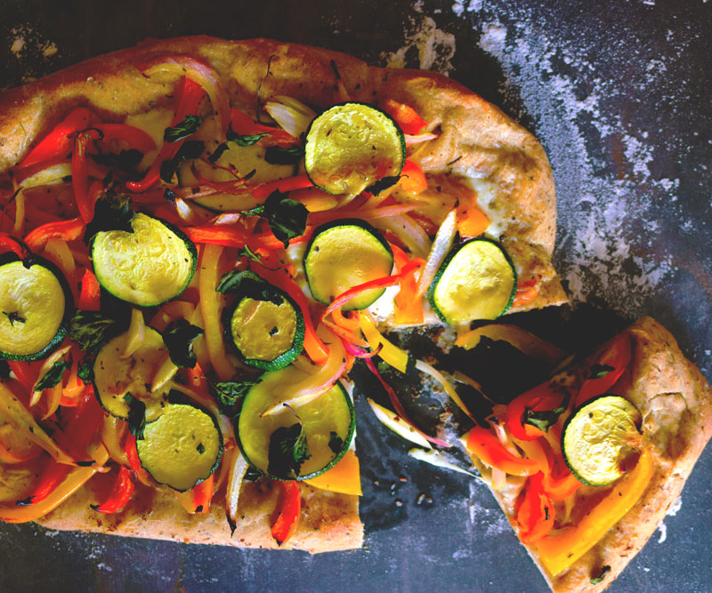 Freshly made Pizza with Peppers & Zucchini on a counter top generously dusted with flour