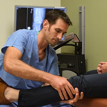 Orthopedic surgeon examining patient's knee